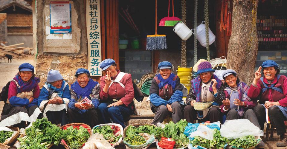 Group of Naxi women selling vegetables in Baisha Village, Lijiang, Yunnan.
