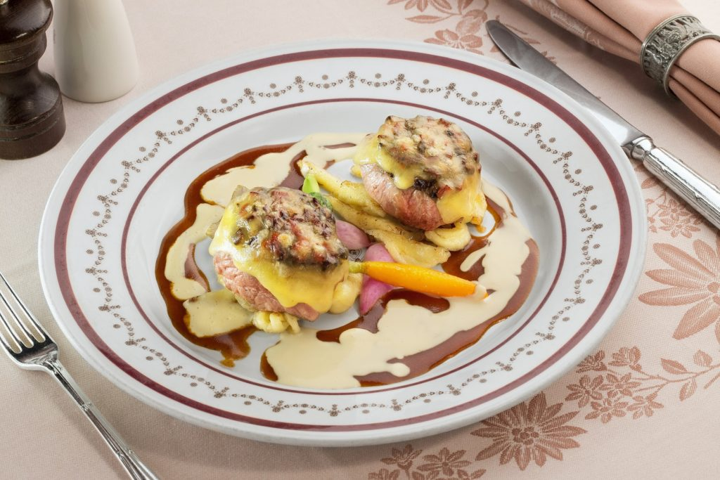 Veal medallions with mushroom sauce on spatzli, gratinated with Emmental cheese at Chesa