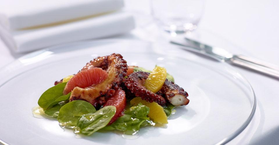 烤地中海章鱼和柑橘沙拉,铺上一层精选的小菠菜叶