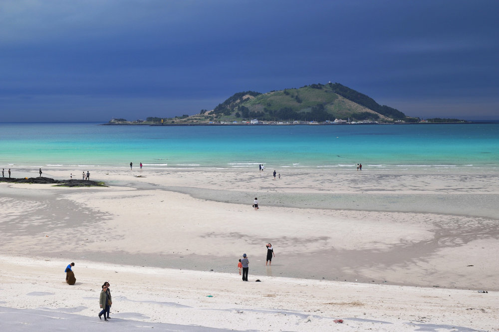 White sand and crystal blue waters on Jeju's Hyeopjae Beach.