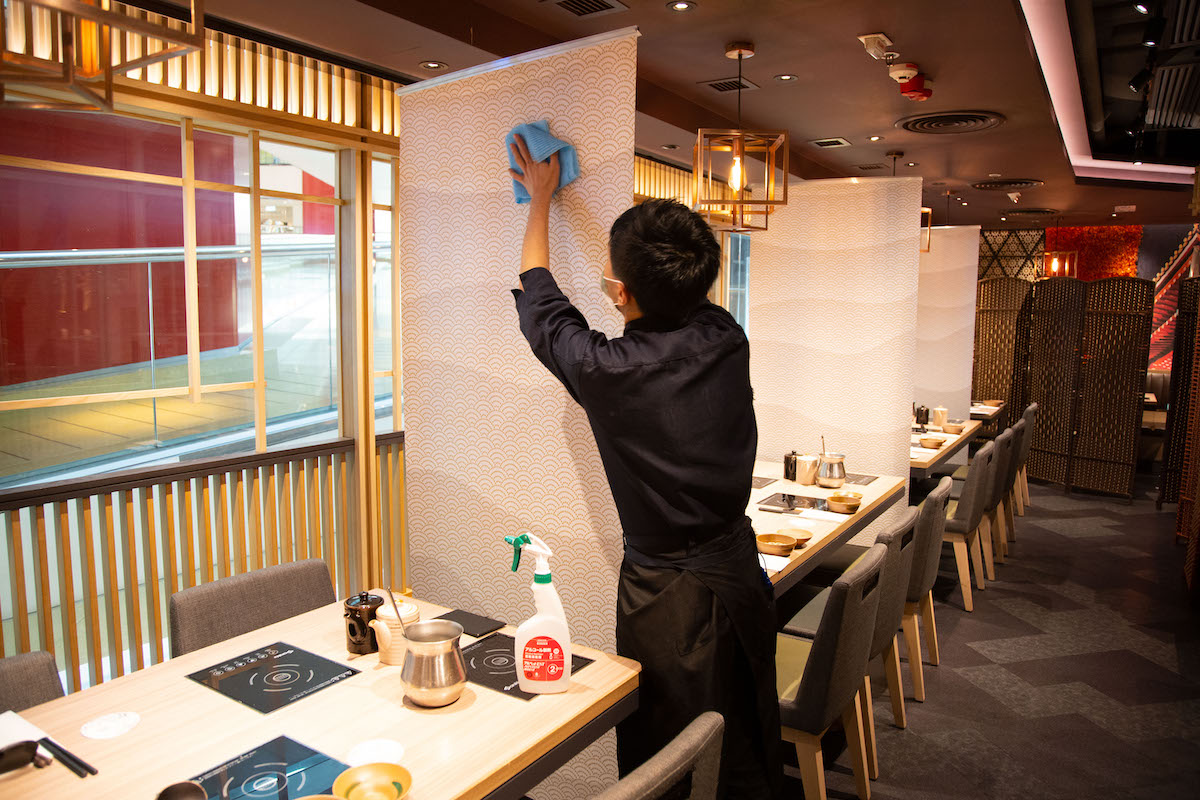 An employee at On-Yasai cleans the partitions used to separate diners